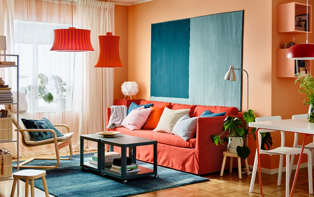 ein modernes wohnzimmer mit orangefarbenen w nden und br thult 3er sofa mit bezug vissle rot. Black Bedroom Furniture Sets. Home Design Ideas