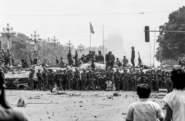 【寫真・図版】1989年6月4日、北京の天安門広場近くの長安街で1人の市民が捕まり、大勢の兵士の前で ...