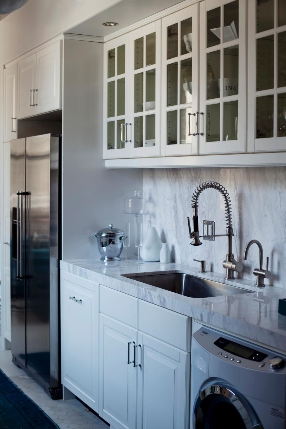 A thick slab of marble tops the kitchen counter and extends across ...