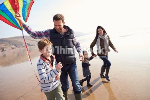 Family Running Along Winter Beach Flying Kite Having Fun Together
