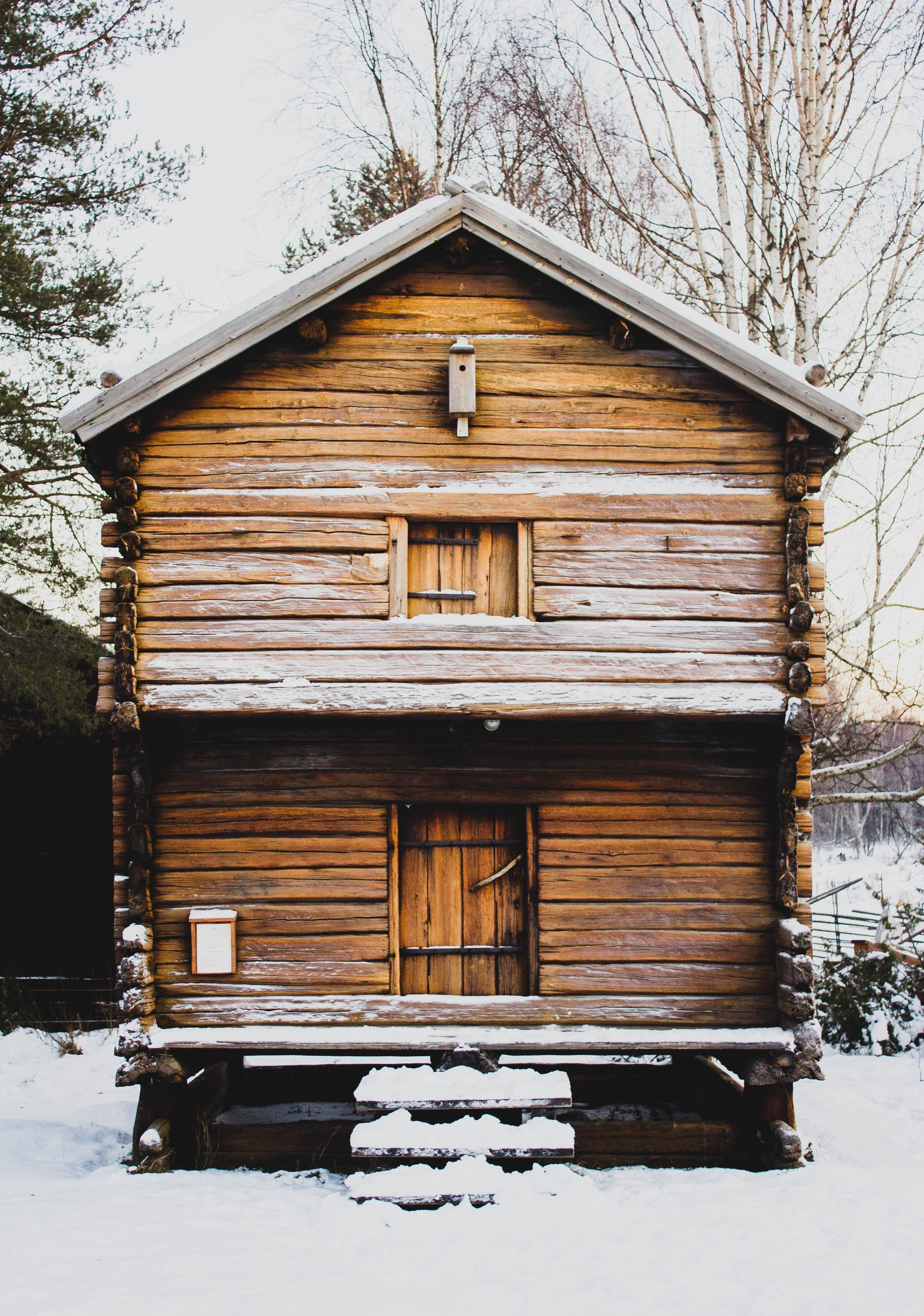 A small twostorey log cabin with steps leading onto the