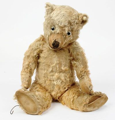 """Chiltern Hugmee golden mohair Teddy Bear, British, late 1920's/early 1930's, clear glass eyes with black pupil and remains of painted backs, shaven muzzle with black vertically stitched nose with raised outer stitch, fully jointed, velveteen pads with card lined feet, black claw stitching, areas of balding to torso, faded and worn overall, left paw pad is split around edge, otherwise Good, 22""""/56cm."""