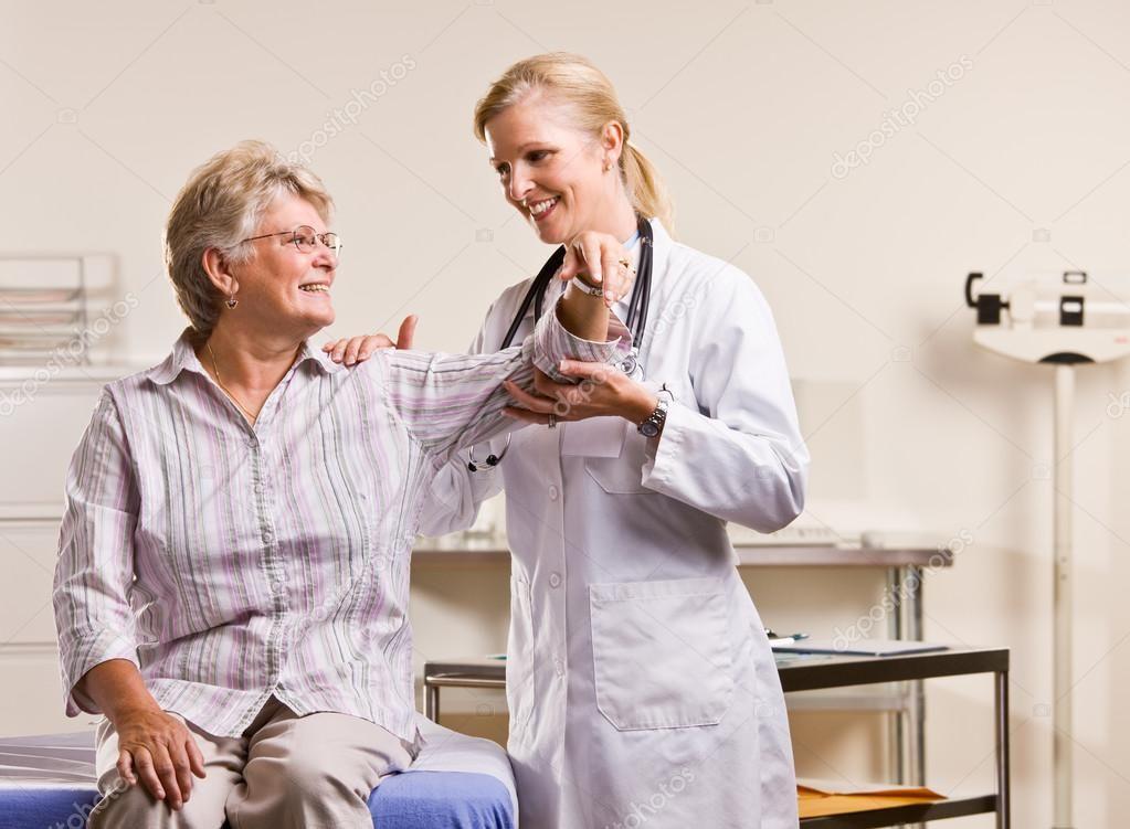 Doctor checking senior woman arm Stock Photo , Sponsored