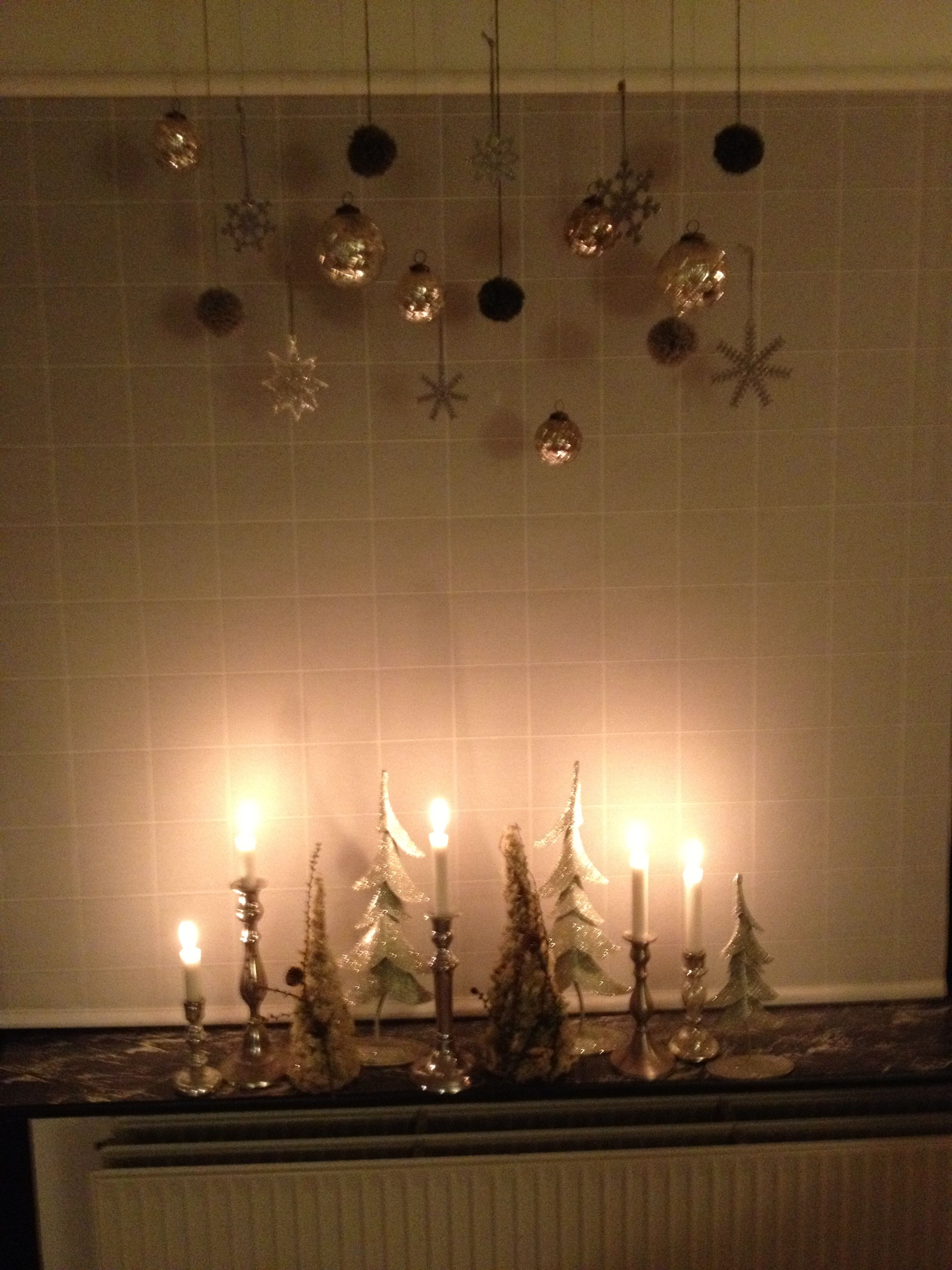 Diverse ophæng (uld pomponer, glaskugler, stjerner) over lysestager. Lysene får ophængene til at snore. / Ornaments and candles. The candles make the ornaments spin.