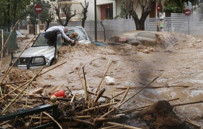 Um homem resgata uma mulher de seu carro em uma estrada inundada no subúrbio de Atenas