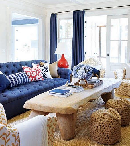 Living room. Navy blue sofa. Orange/red accents. Print yellow chair ...