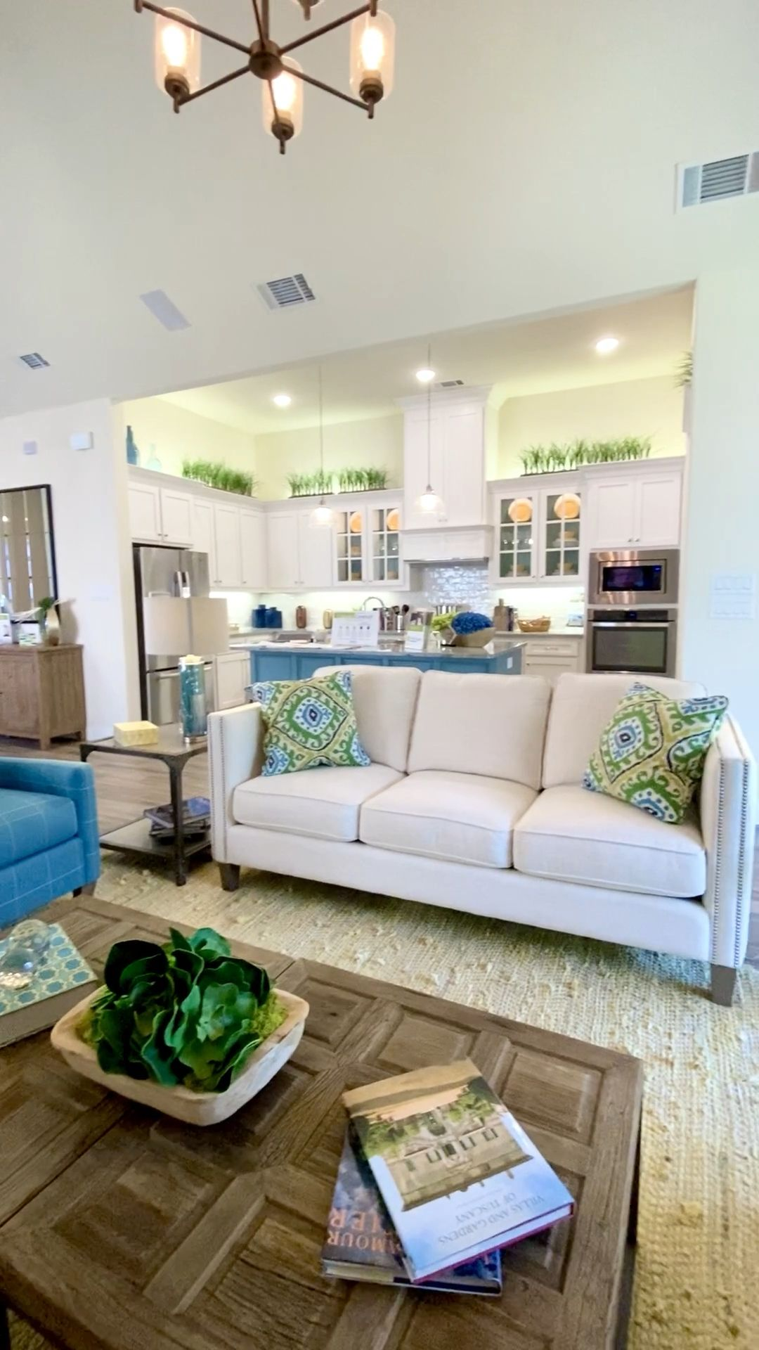 White kitchen cabinets open to the dining and living room with blue and green decor.  Click to see more decorating ideas and model home photos.... Learn how to decorate your own home... THE DECORATING COACH  #decoratingideas #kitchencabinets #livingroomdesigns