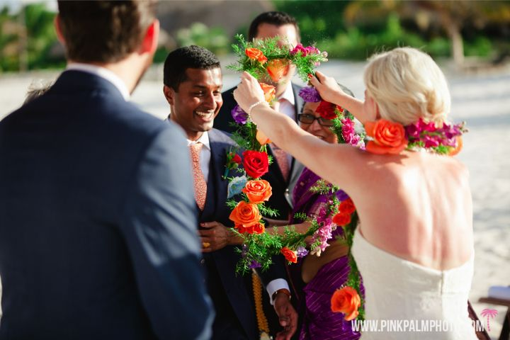 Colorful garlands in purple red and orange were placed around the bride and groom in this non traditional Indian wedding. #mishkadesignsmexico #secretsmaroma