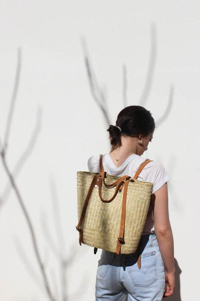 handwoven palm leaf bag with leather straps. wear as a