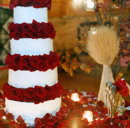 An impeccable Wedding cake accented with stunning red ...