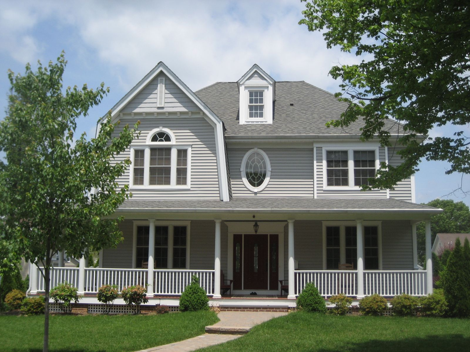 A new home with a gambrel roof dormer window and wrap around porch