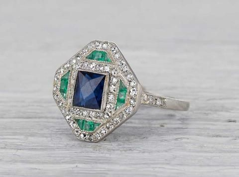 Antique Edwardian ring made in platinum and centered with an approximately 1.12 carat sapphire and accented with emeralds. Circa 1925. A bold and graphic ring with classic Deco flare. Diamond and gold mining has caused devastation in areas such as Africa, wreaking havoc on delicate ecosystems and communities. Choosing to go vintage, you are eliminating the need for more mining and lessening the demand for new diamonds.