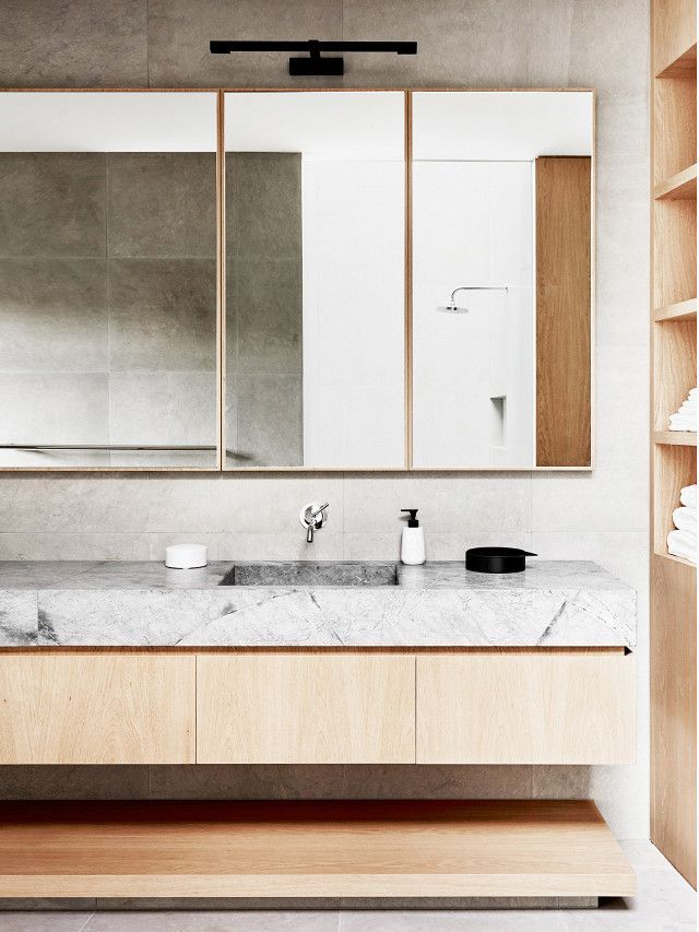 This is how your bathroom should look according to your age warm minimalist bathroom with a light wood vanity with a marble top light wooden mirrors and a mounted black sconce aloadofball Image collections