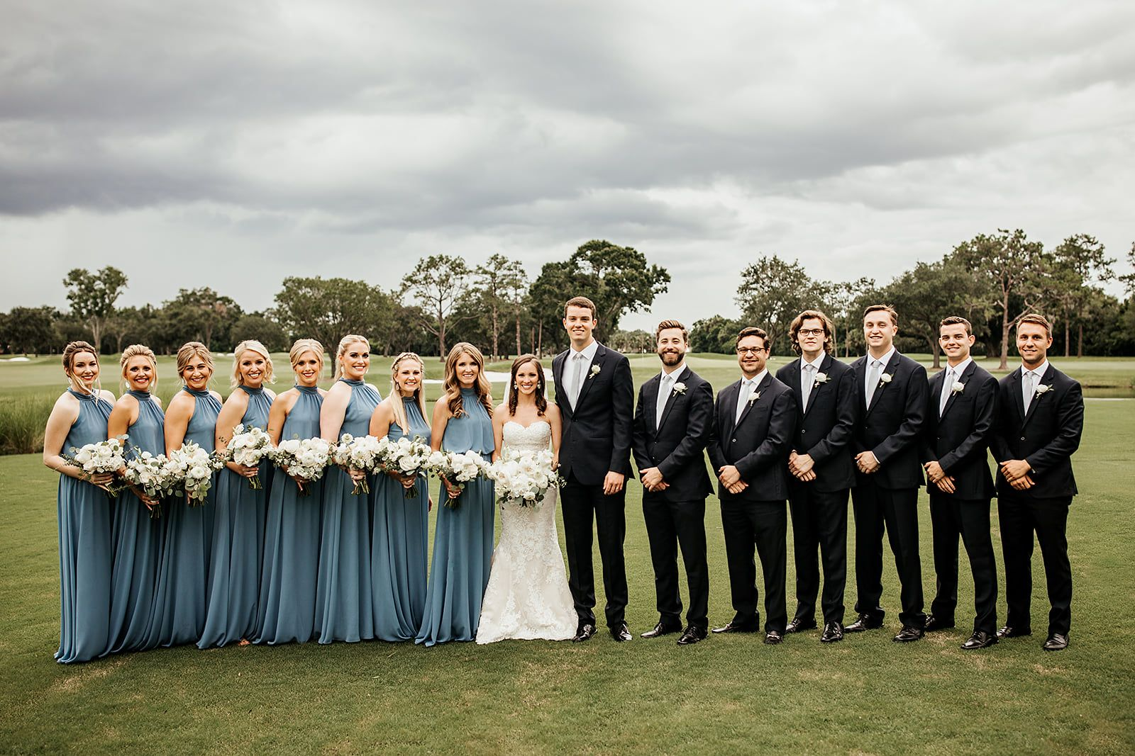 Wedding Party With Groomsmen In Black Tuxedos And Light Blue Ties And Bridesmaids In Dusty Blu Slate Blue Wedding Blue Groomsmen Dusty Blue Bridesmaid Dresses [ 1067 x 1600 Pixel ]