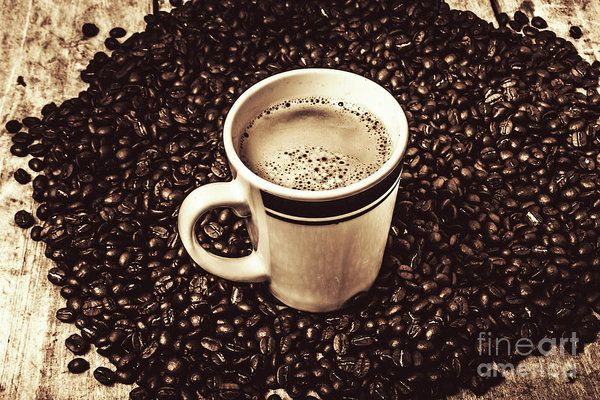 Traditional coffee shop still on a cup placed amongst a heap of dark brown coffee beans. The art of brewing by Jorgo Photography - Wall Art Gallery
