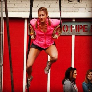 Woman doing muscle-up. Rings.
