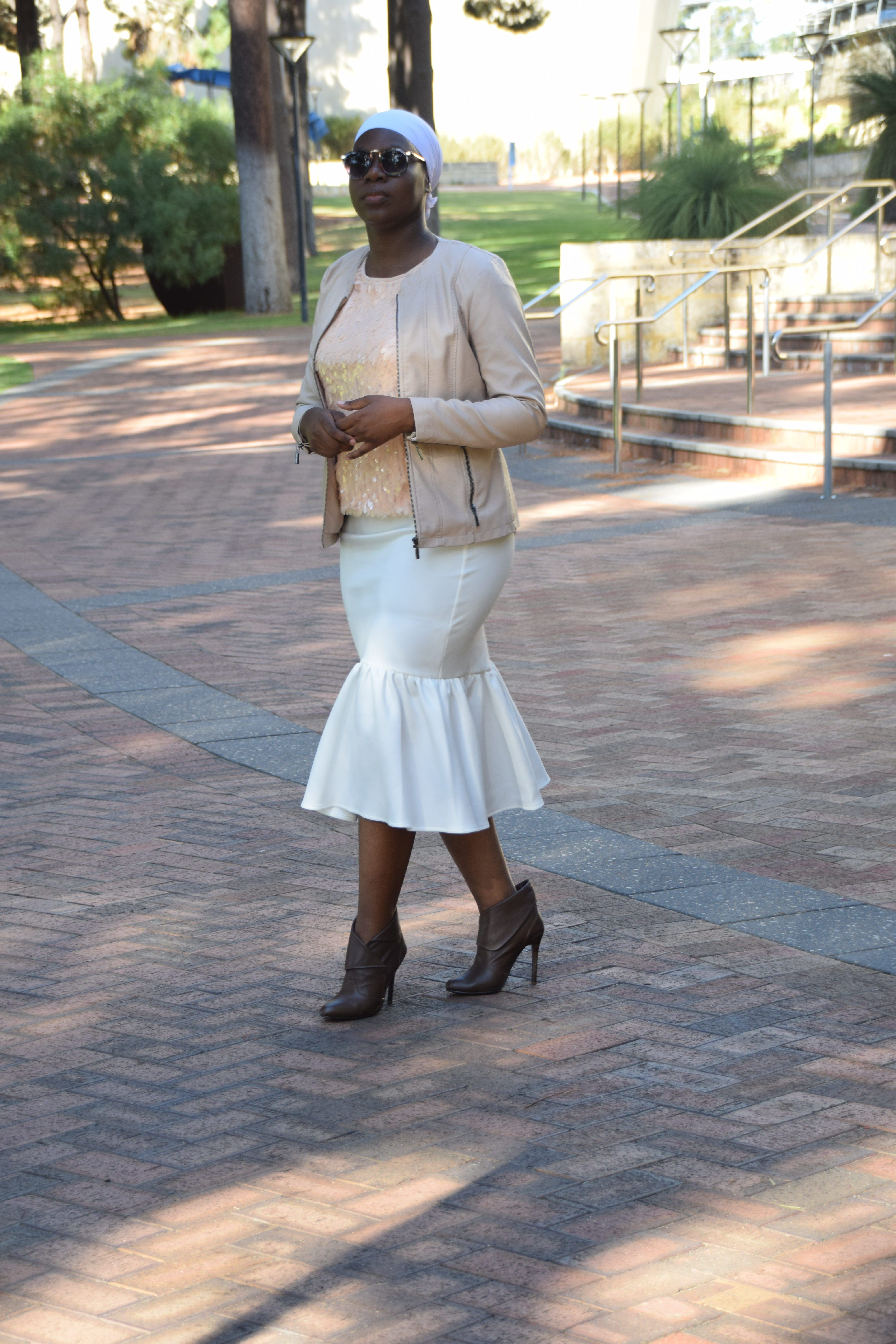 6c6557bb5 white pencil skirt with ruffle detail, brown ankle boots, peach sequin top  and beige leather jacket
