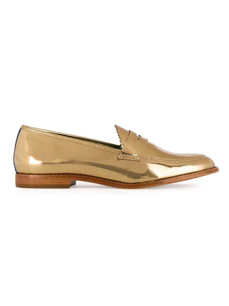 2083c8e7f Mocassim de couro metalizado dourado, Blue Bird Shoes. Possui bico  arredondado, detalhe de recortes, acabamento em viés e salto baixo em  madeira.