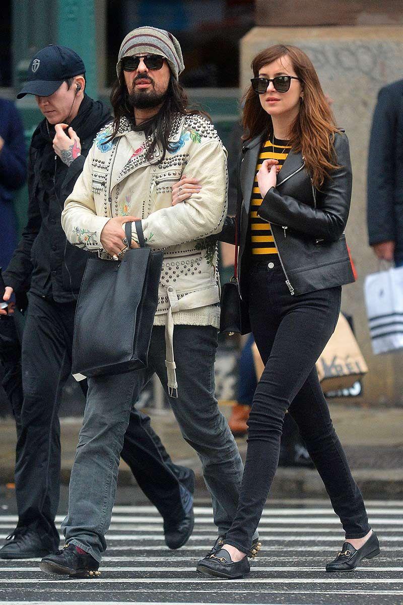 Dakota Johnson paseando por Nueva York con Alessandro Michele, director creativo de Gucci. Con cazadora de cuero, jersey de rayas en negro y naranja, vaquero negro, mocasines con hebillas, de Gucci y gafas de sol XL.