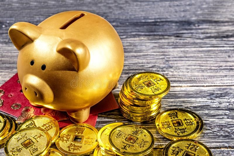 Piggy bank with golden coins and red envelopes on the