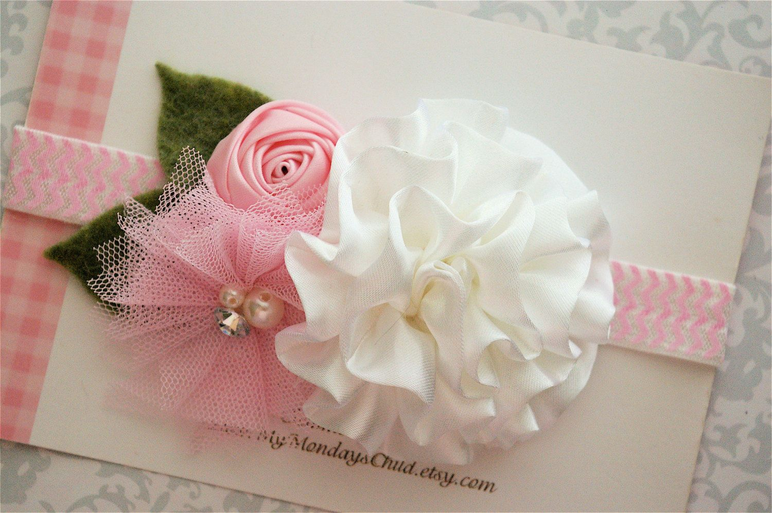 This satin and tulle flower headband is adorable! The white ruffled satin flower has lots of softly gathered layers with a pink satin rosette and tulle flower with a pearl and rhinestone center! The flowers are attached to a 5/8 inch elastic pink chevron headband and are backed with felt. Two wool felt leafs are tucked into the side. Sweet for girls of all ages and perfect with the Matilda Jane Good Hart collection and so many little outfits! This item can also be made into a hair clip or…