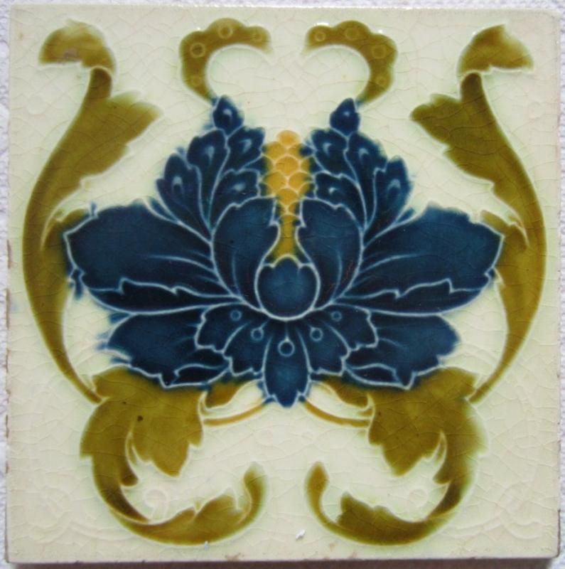 Energetic art nouveau design depicting deep blue poppy with leaves unfurling on a cream ground from the English maker T.A. Simpson, c. 1903. Tile is in very good condition with light edge wear as shown but otherwise very glossy wonderful glaze.