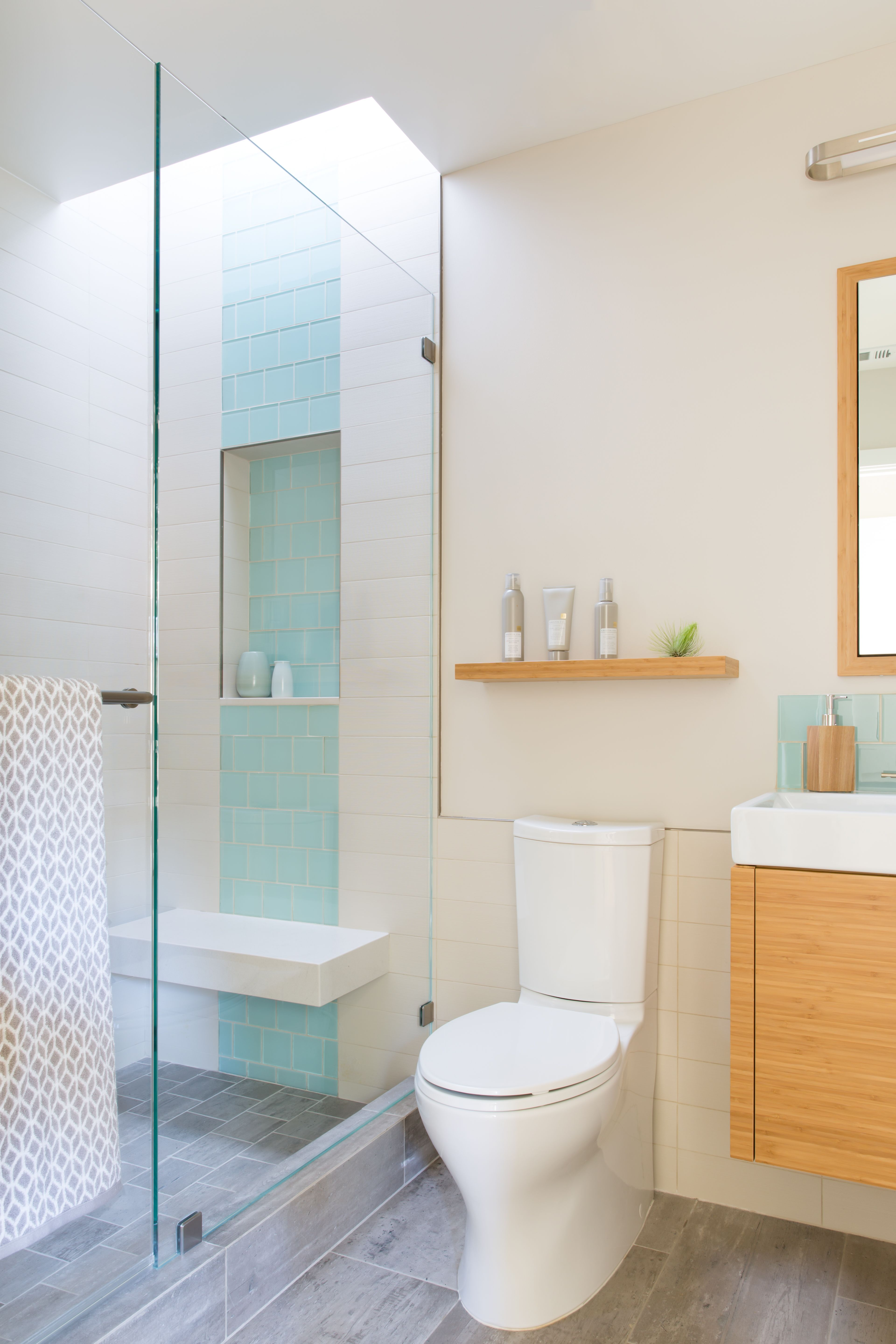 Contemporary light filled bathroom with sea green glass tile accents ...