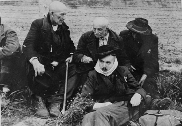 Elderly Jewish men sit on the grass in Auschwitz-Birkenau prior to being sent to the gas chambers. The man in front wears a scarf to cover his forcibly shaven face.
