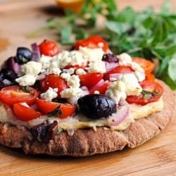 Greek Pita Pizza. A whole wheat pita topped with hummus, red onion, tomatoes, kalamata olives, and feta in a red wine vinegar dressing. Heavenly!