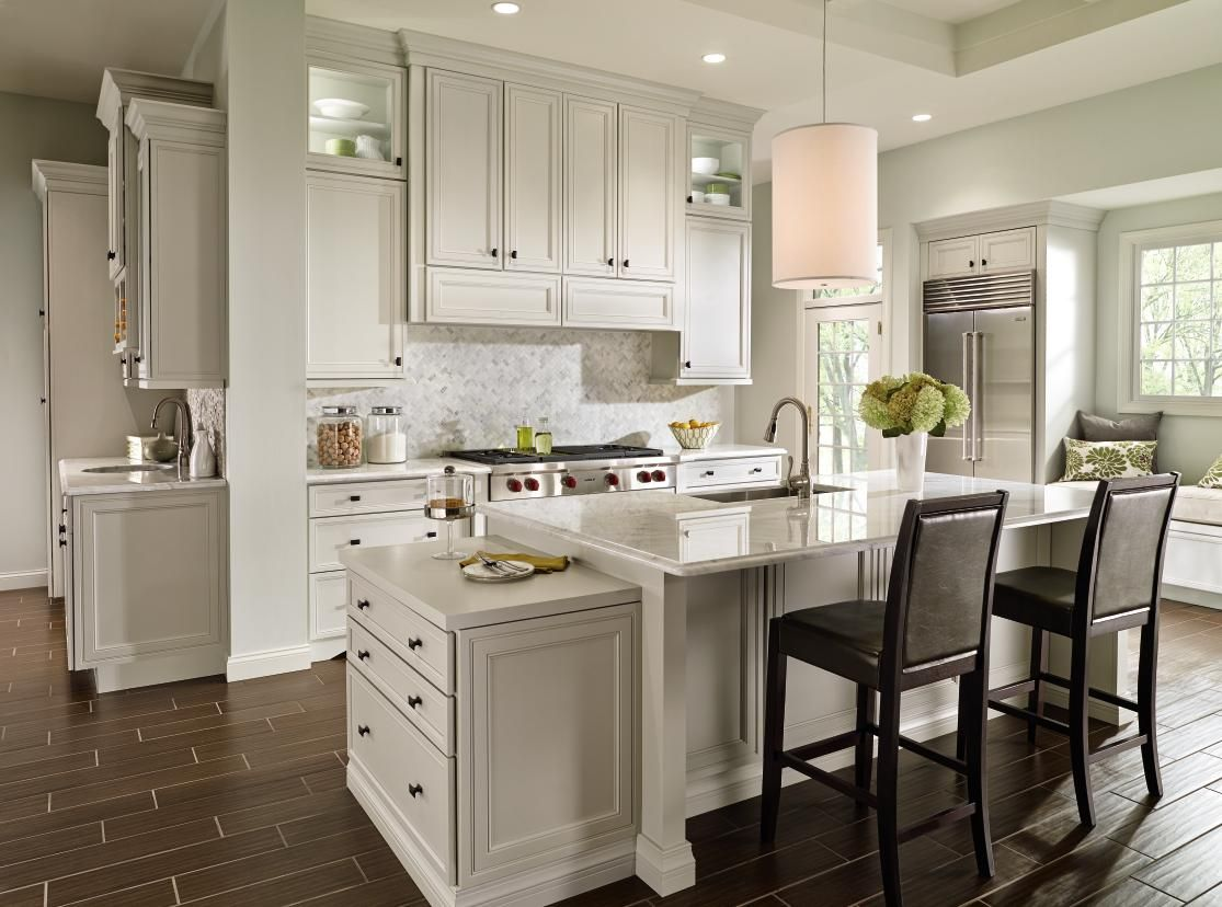 Decora Cabinetry S Braydon Manor Door Style In Crushed Ice Finish Gives This Kitchen A Kitchen Cabinetry Design Off White Kitchens Off White Kitchen Cabinets