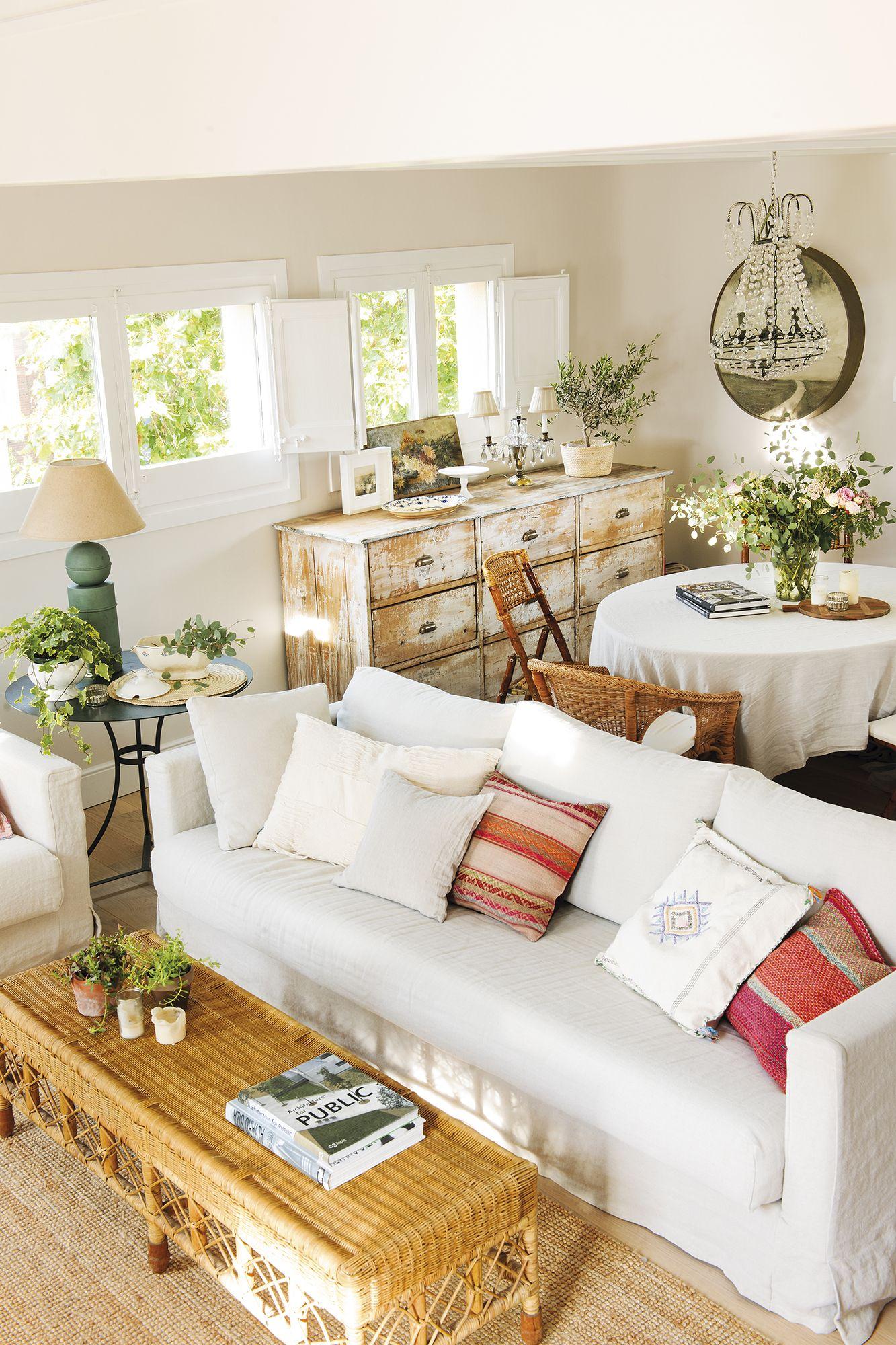 Pequeño salón con sofá blanco y comedor con sillas de fibras junto a ...