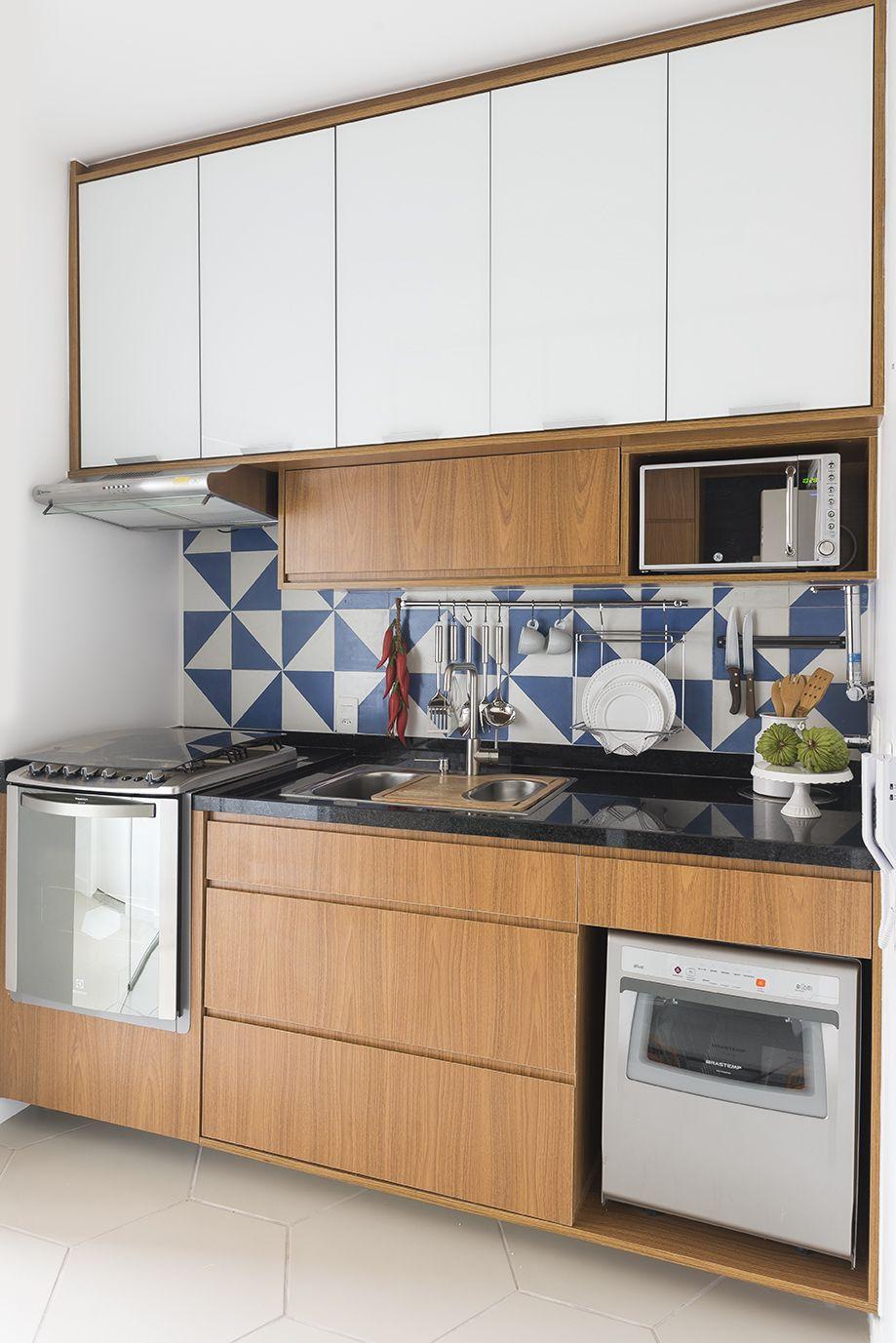 Cozinha com parede em ladrilho hidráulico, móveis em padrão madeira ...