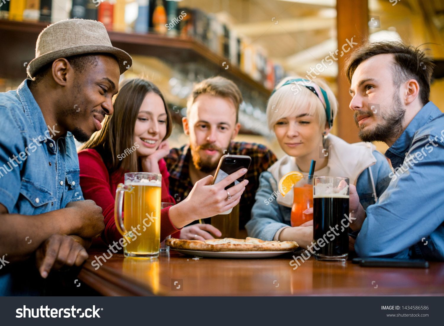Young friends sharing pizza in a indoor cafe Multiracial happy millennial friends having fun eating pizza together laughing at funny joke and using smartphone
