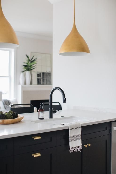gold lights illuminate a black shaker kitchen peninsula accented with brass ha replacing on kitchen remodel gold hardware id=81746