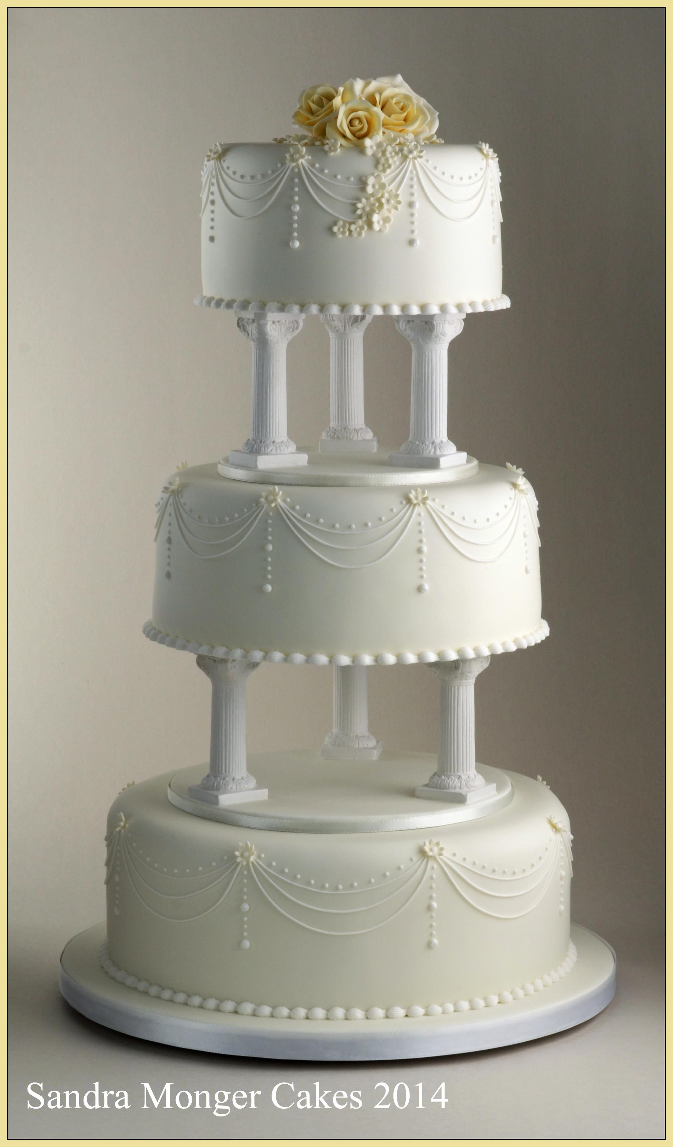 4 tier wedding cake with pillars classic pillar wedding cake with piped swags and flowers 10423