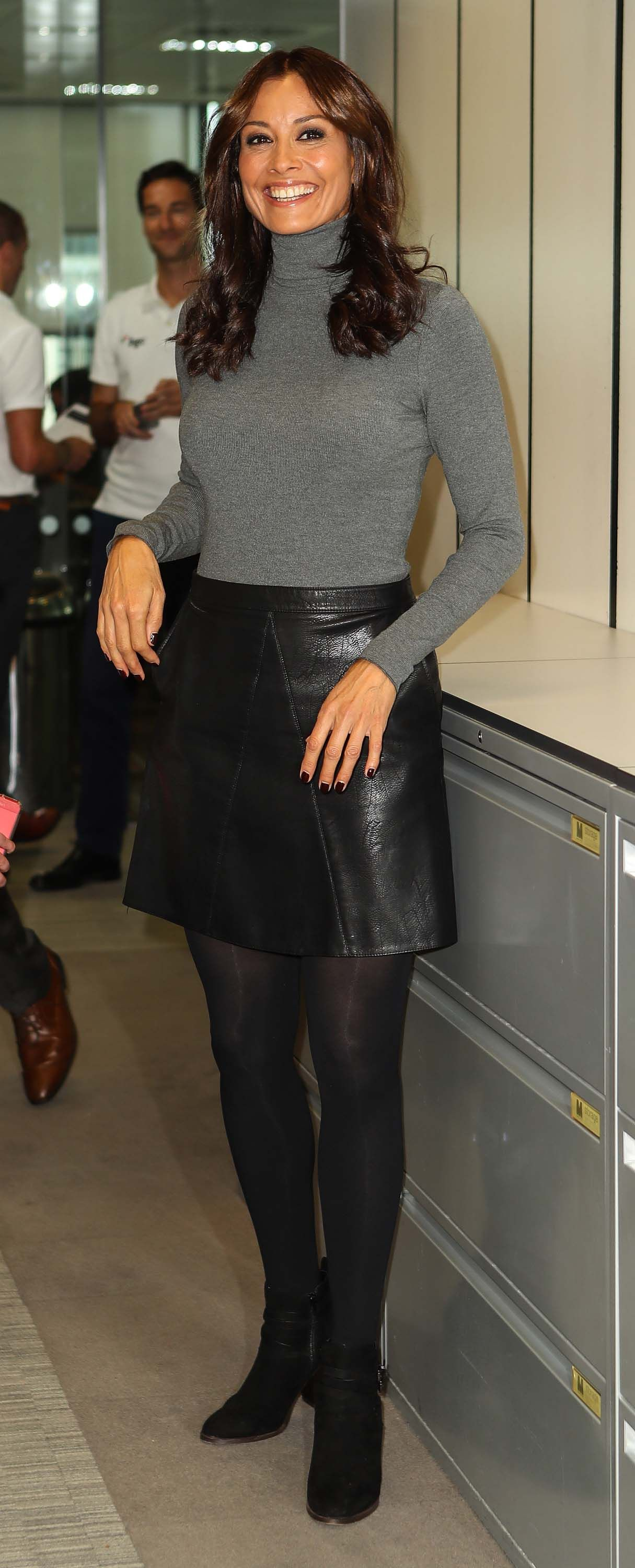 27c113e168 Melanie Sykes attends BGC Charity Day in tight gray pullover black leather  skirt and ankle boots
