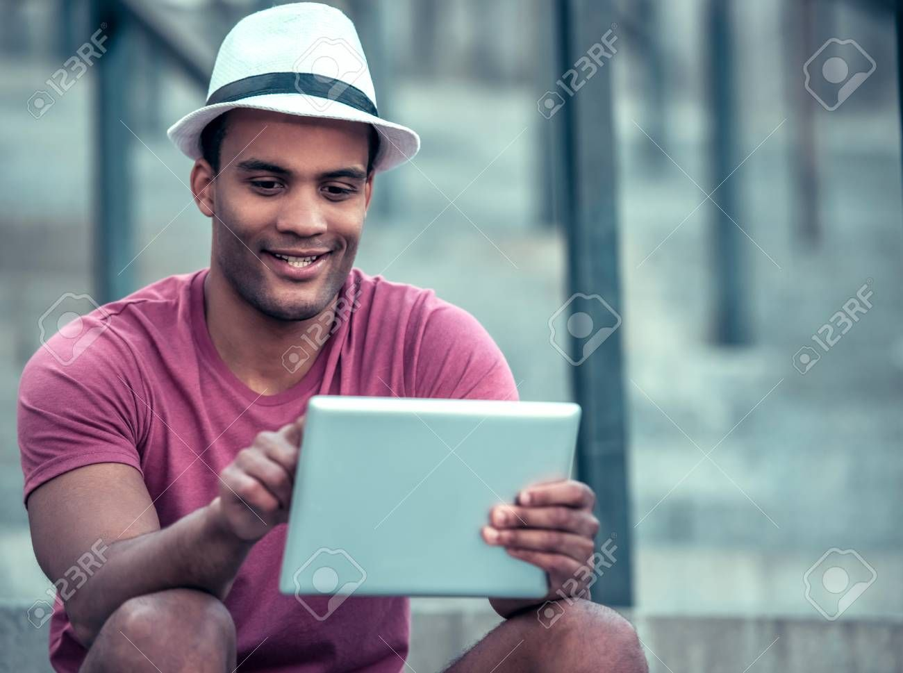 Afro American man is using a digital tablet and smiling while sitting on stairs during city walk ,H