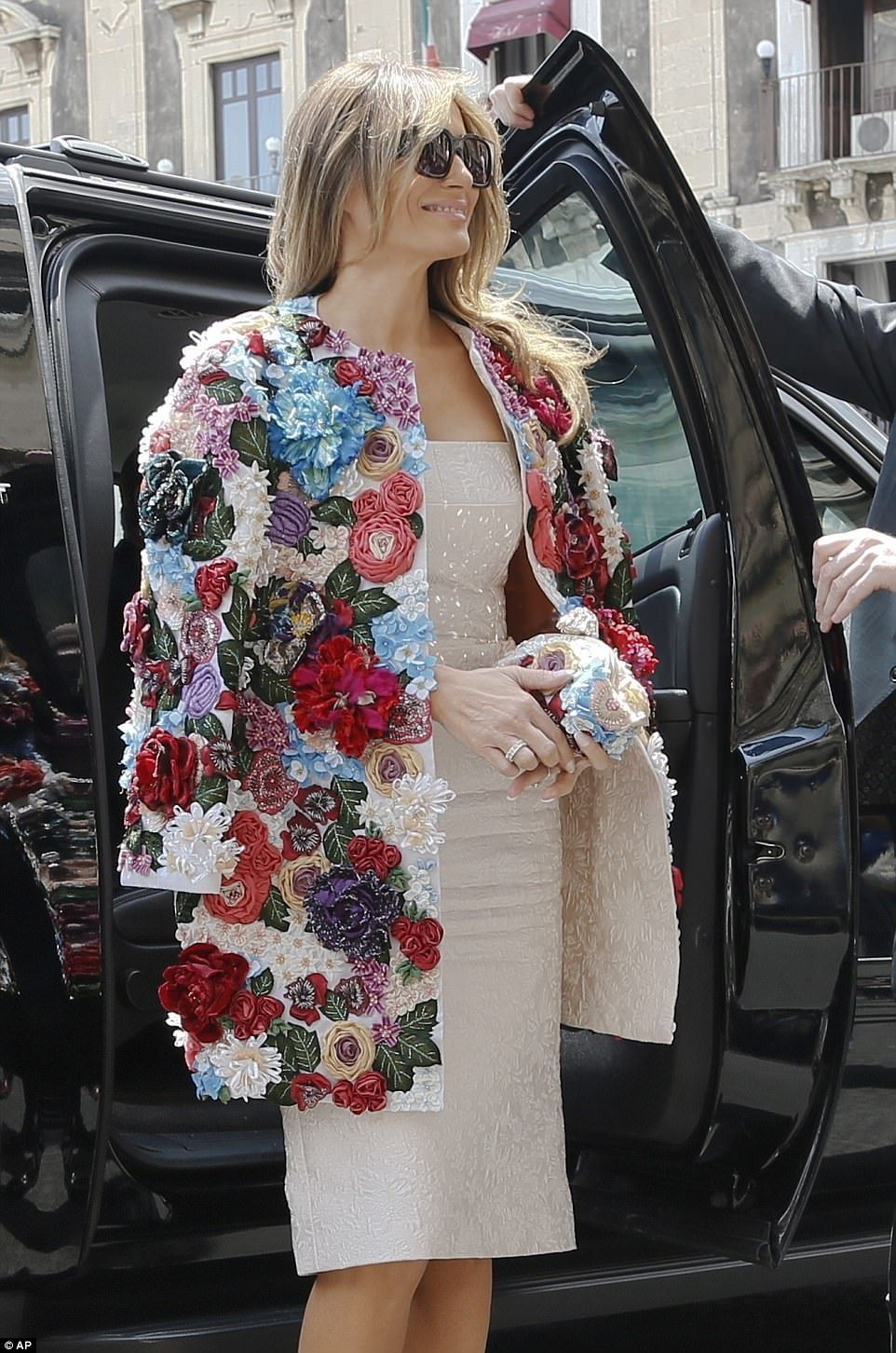 a68a8ec58f5 Melania s form-fitting Dolce   Gabbana dress matches the lining of her statement  coat
