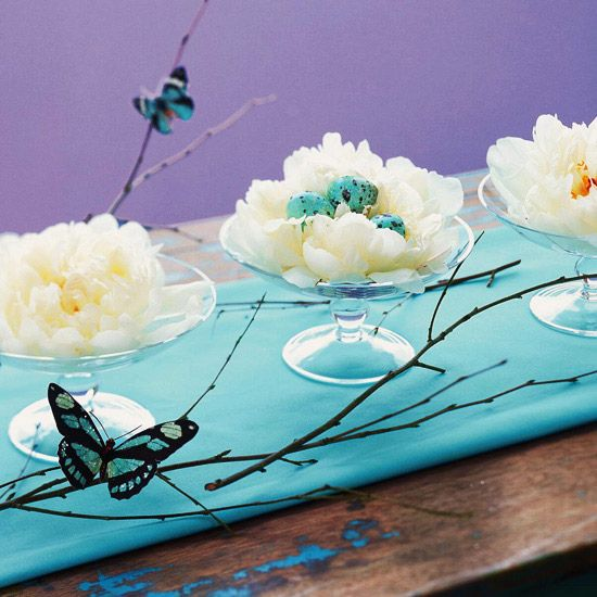 Blue Easter Table Runner              Give your Easter table a pop of spring color with this table runner centerpiece. Place white flowers in small footed dishes, and then add decorated eggs and festive candy to the arrangements. To finish the fresh spring look, hot-glue faux butterflies to branches placed around the dishes