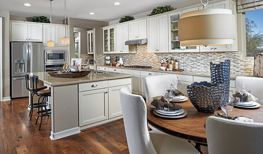 Bright White Cabinets Are Complemented By A Neutral Mosaic
