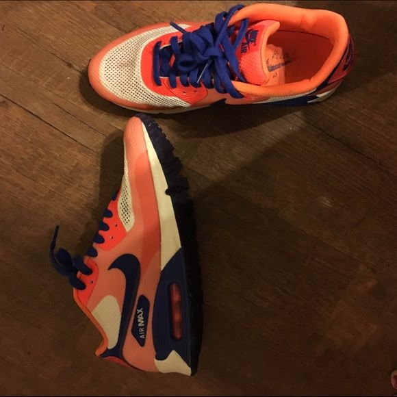 Woman's orange and blue Nike Airs Perfect condition except for that one little spot on the left shoe. They say size 9.5 but I wear a size 8.5-9 and they fit me perfect. Nike Shoes Athletic Shoes
