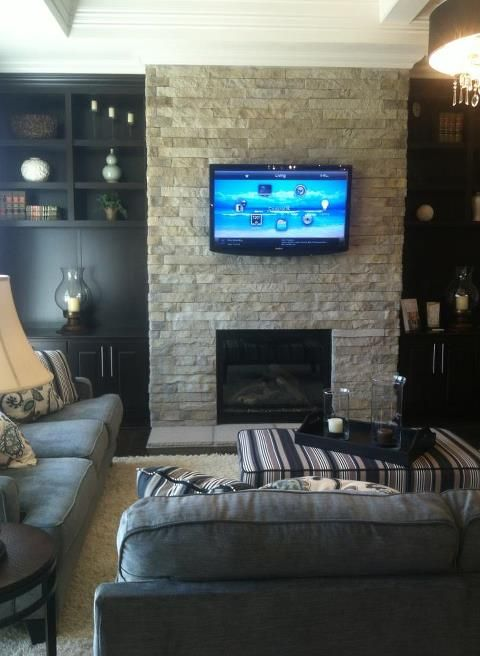stacked stone interior fireplace and flat screen tv with dark wood shelving