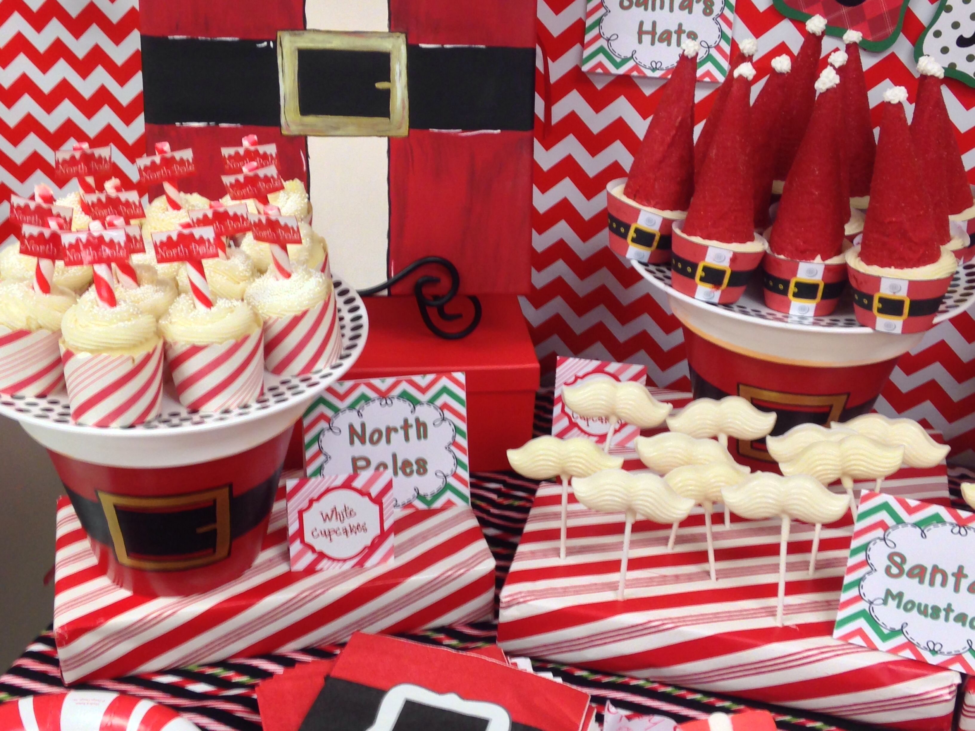 Polar Express cupcakes.  Santa's suit wrappers over red velvet cupcakes with sugar cone hats. Hats were dipped in red melting chocolate and sanded with red sanding sugar. North Pole cupcakes were vanilla cake with butter cream icing.