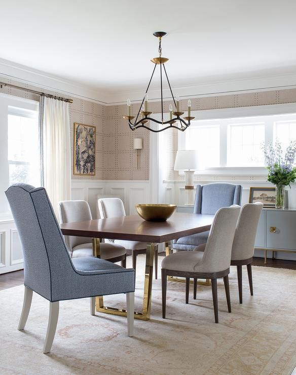 Blue wingback head chairs sit on a gold wool rug at a wood and brass dining table seating gray ...