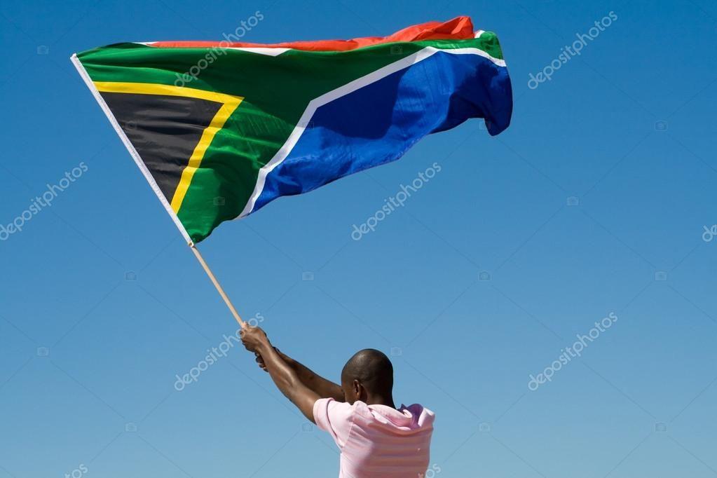 Африканских человек, размахивая флагом Южной Африки против голубого неба