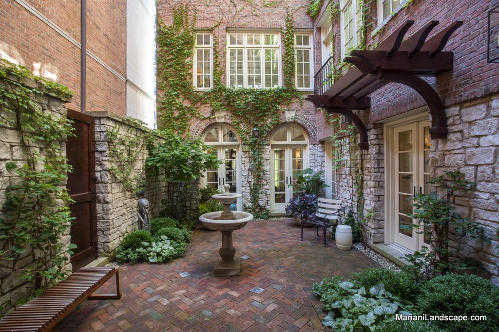The rich tone of the clay pavers complements the stone and for French style courtyard ideas