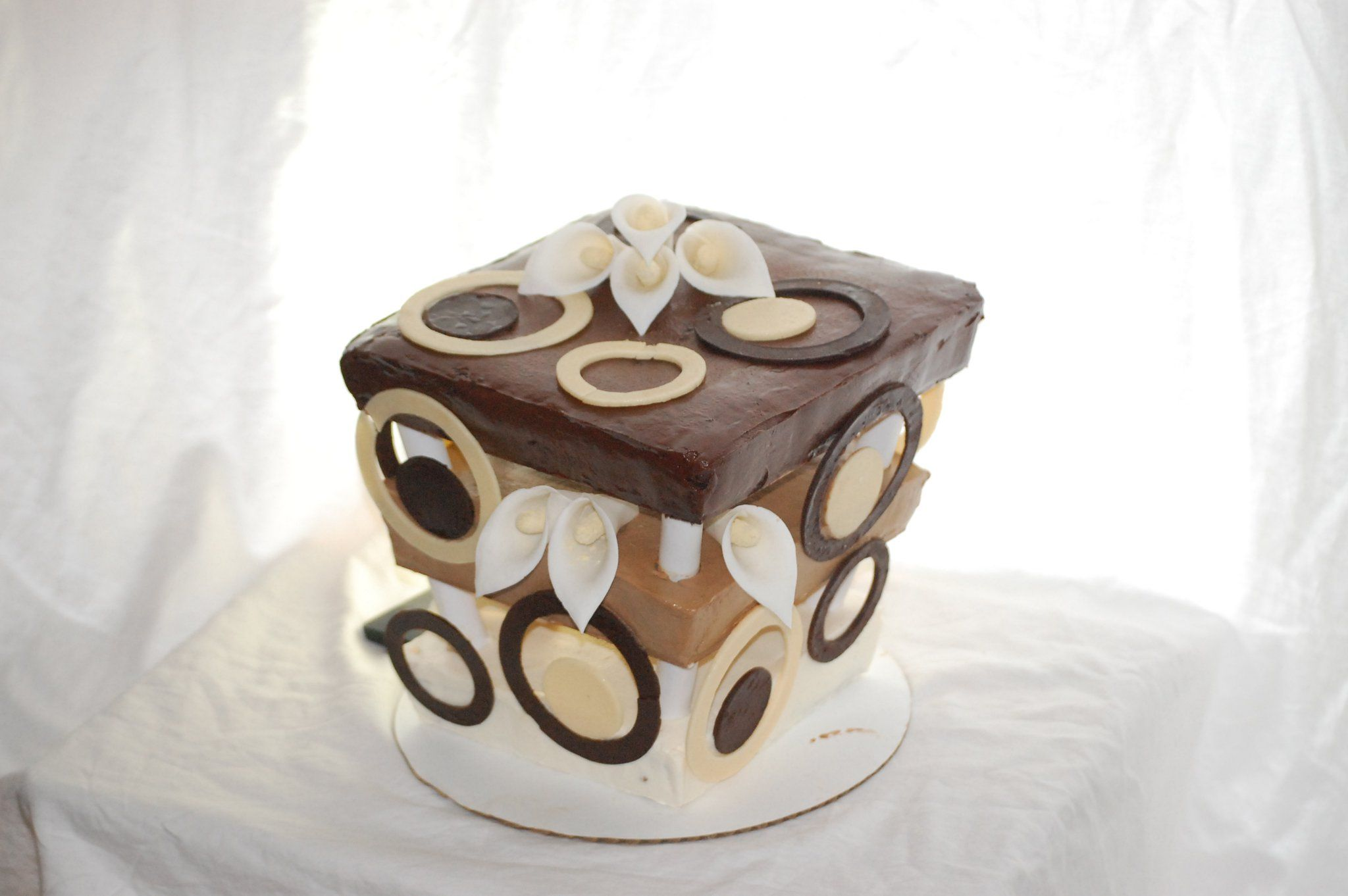 1st tier - banana nut w/ cream cheese icing. 2nd tier - yellow cake with caramel cream icing. 3rd tier - dark chocolate cake with rich chocolate icing. Adorned with white and dark chocolate rings and gum paste calla lilies.