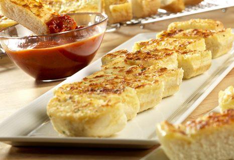 Mozzarella Cheese Bread Sticks- Aromatic garlic bread, topped with mozzarella cheese, is served with a rich Italian tomato sauce for dipping.