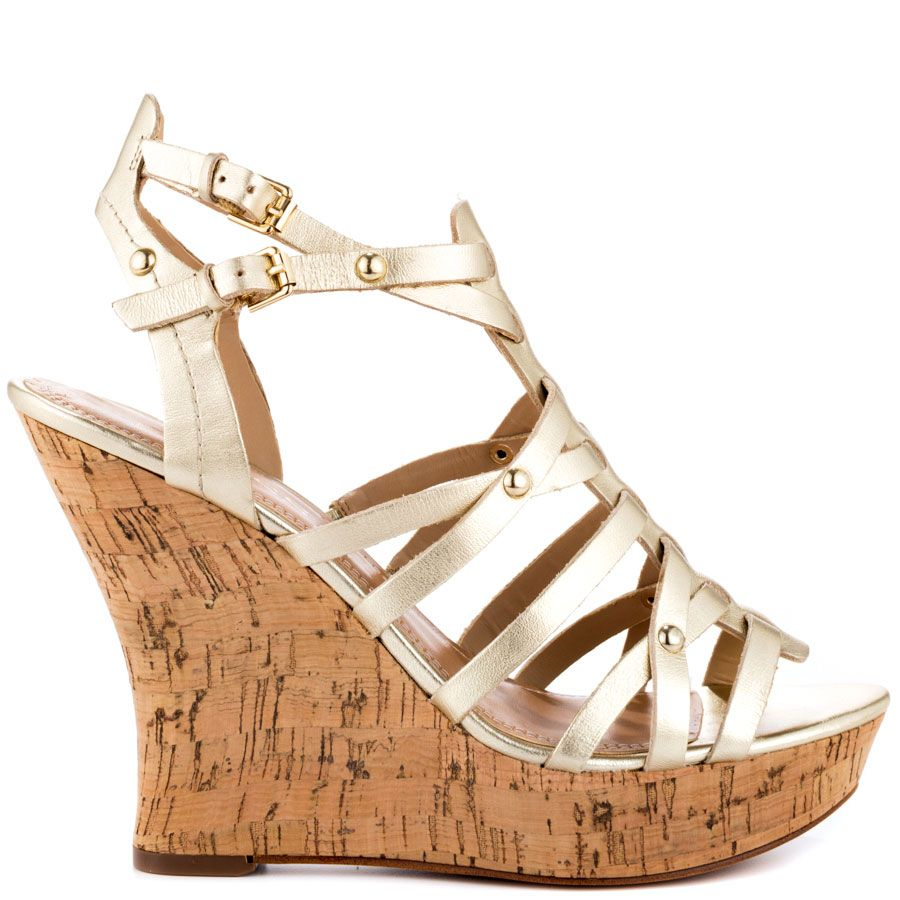9e3af4e8921 This Guess style features a gold leather upper consisting of fun  overlapping straps. A 4 3 4 inch wedge and 1 inch platform ...