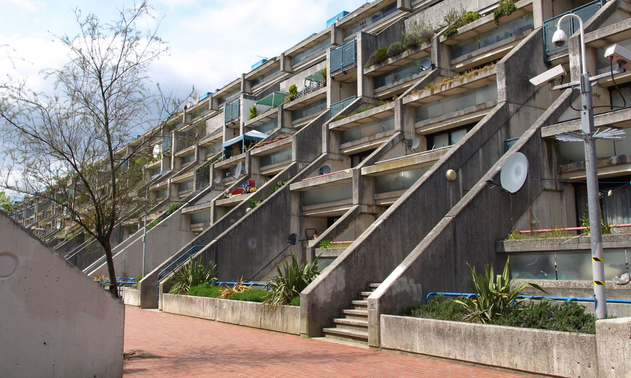 """Neave Brown designed two of the finest council housing schemes of the period – the Fleet Road flats in 1967 and Alexandra Road, from 1968–78. A bold reinvention of the London terrace, Alexandra Road curves along the edge of a railway line, extending concrete fins down to a street to define private terraces. It was  Brown's ambition to ""return to housing the traditional quality of continuous background stuff, anonymous, cellular, repetitive, that has always been its virtue."" - The Guardian"